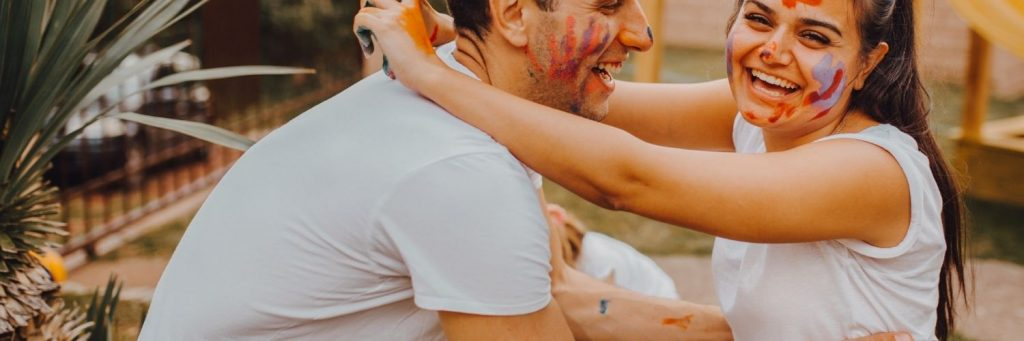 A man and woman holding each other and laughing. They are looking into each others eyes and have paint smeared on their faces.