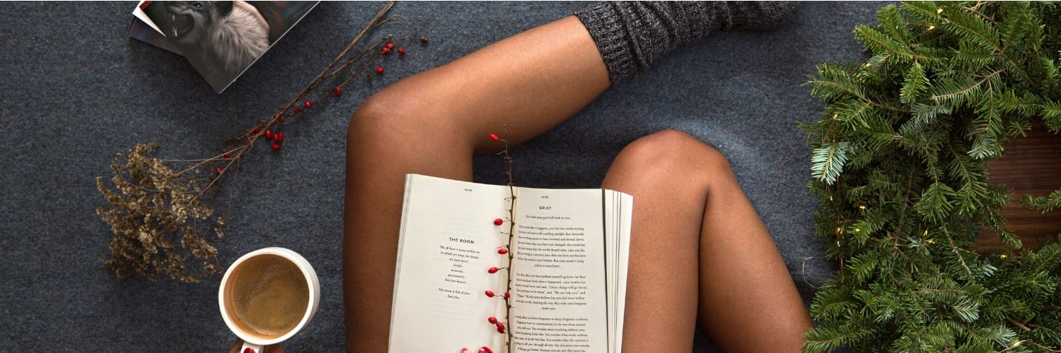 Book on bare legs with tea and pine tree