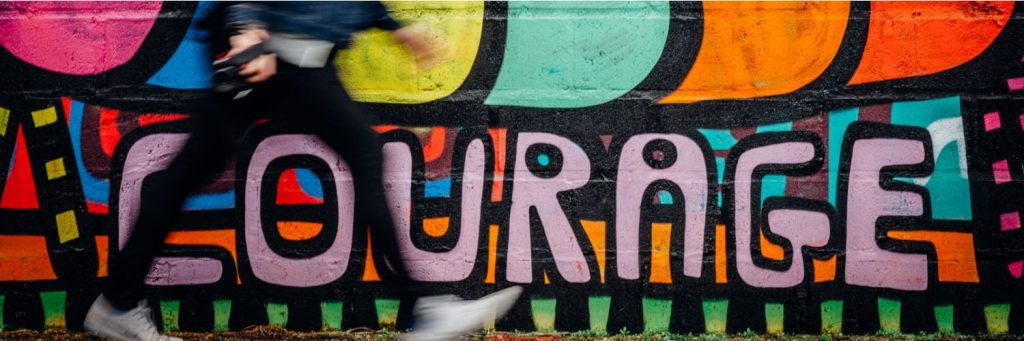 man walks past graffiti of the word courage