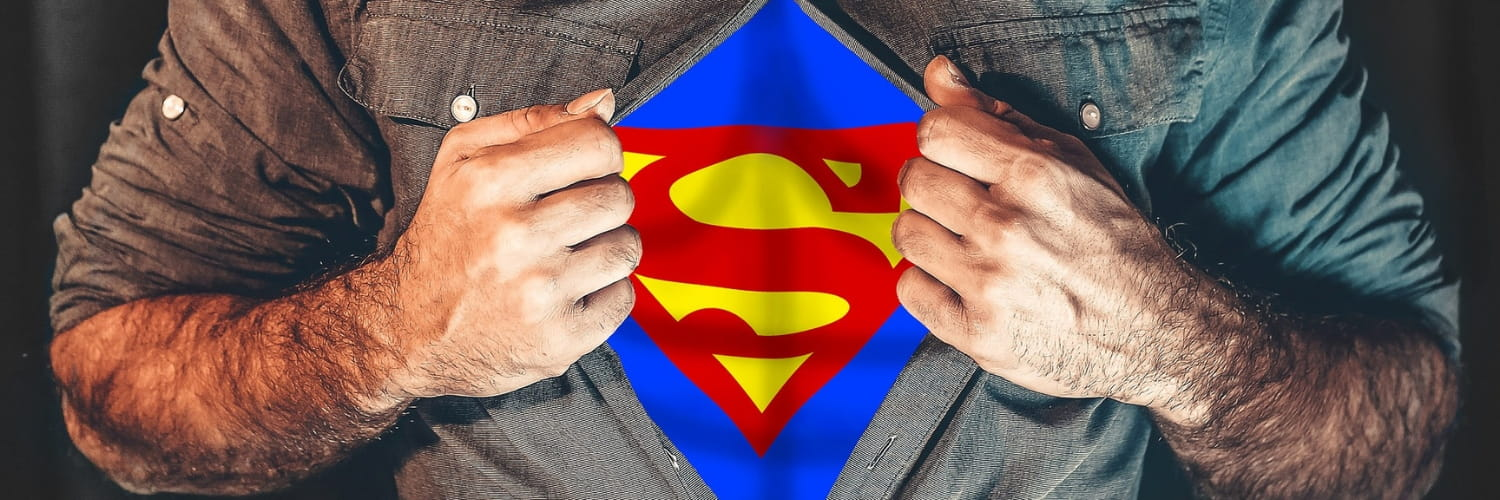 Man ripping open shirt to reveal superman costume.