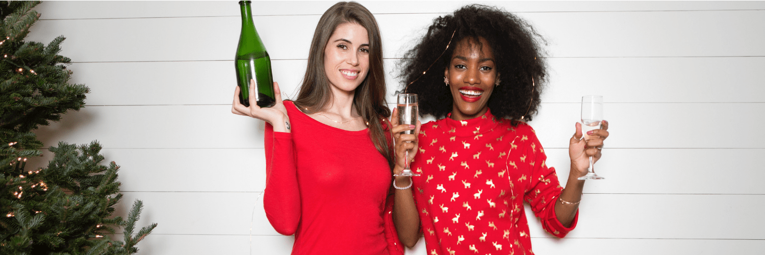 Women with wine wearing Christmas jumpers near a Christmas tree