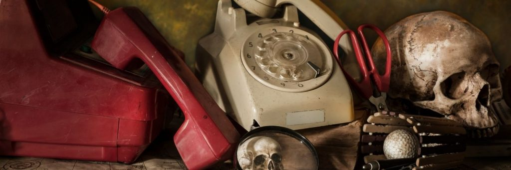 Image shows old fashioned telephone handsets from the 80s on a messy benchtop. They are dusty and there is also a human skull, magnifying glass, golf ball and pen.