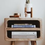 bedside table with books inside, and a plant and a crystal on the top.