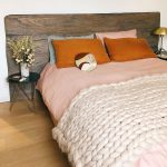 Hygge bed with wooden bedhead, orange pillows, and chunky knit blanket.