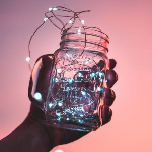 mans hand holding mason jar filled with string lights on sunset background.