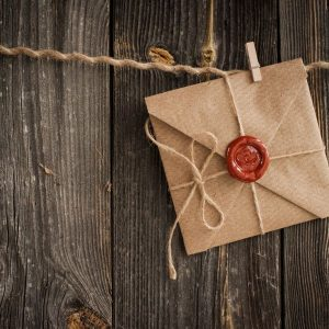 Brown wrapped card sized packet with red wax seal stamped with hearts, pegged to a string on a wooden background.