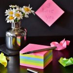 "block of post it notes with pen, note stuck to wall saying ""I love you"" and a jar of white daisies."