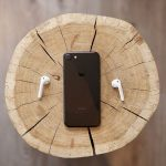 Iphone and airpods on wooden log.