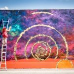 Artist painting multicouloured wall in a spiral from a ladder
