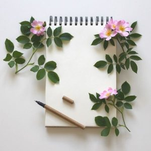 notebook and pen with pink flowers on leafy stems