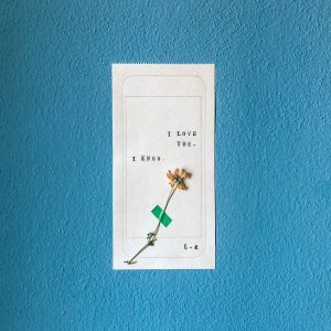"""Note on blue background that says """"I love you"""", """"I know"""" and has a flower stuck to it."""