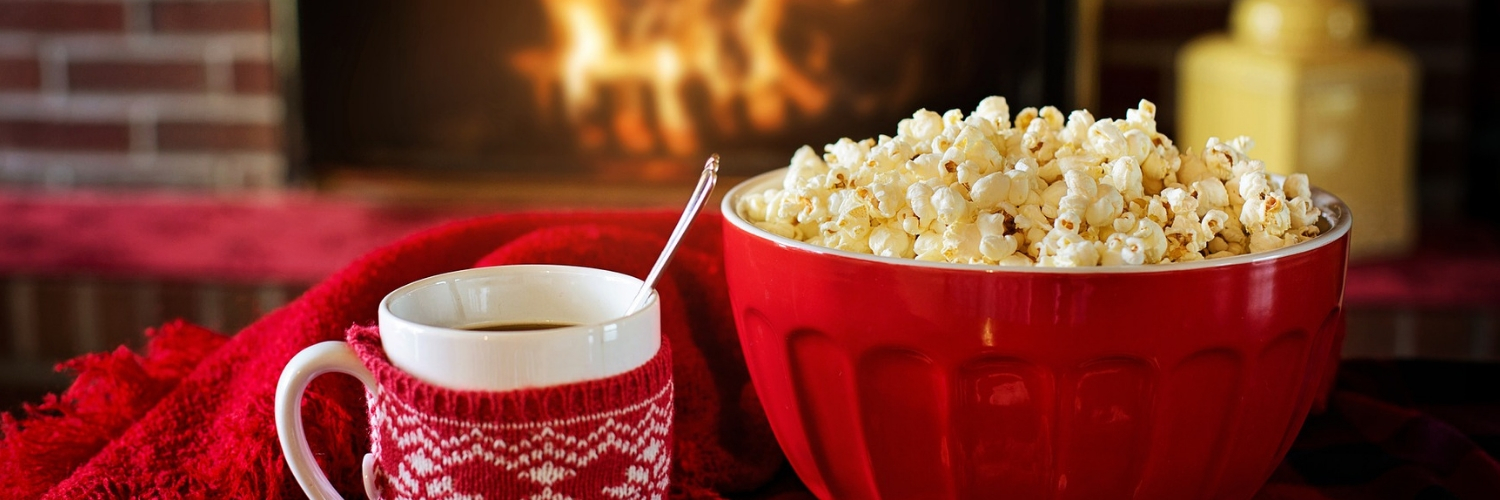 A white mug with a red cosy and a red bowl of popcorn in front of an open fire