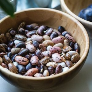 A wooden bowl filled with uncooked borlotti beans.