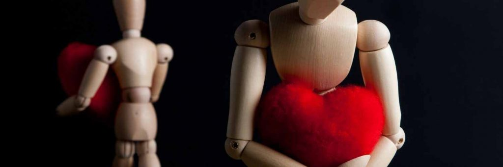 Two articulated wooden drawing model dolls with their backs to each other holding love hearts.