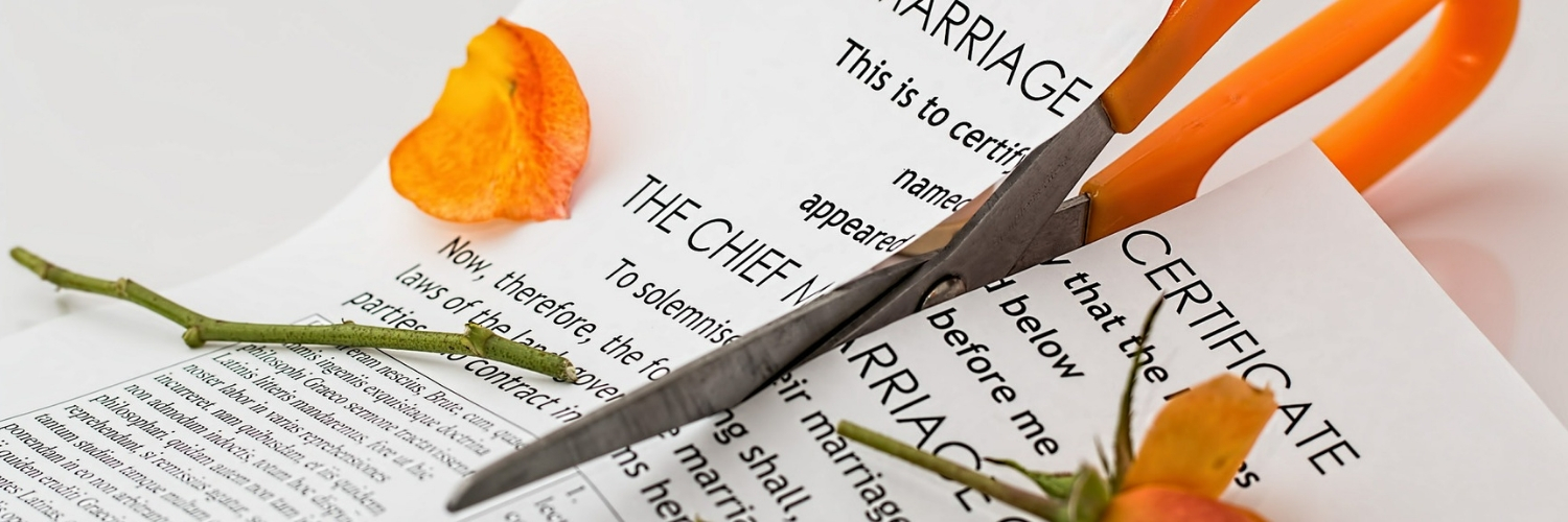 Scissors with orange handles cutting a marriage certificate in half. There is an orange rose on top.
