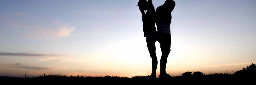 Silhouettes of two people standing back to back in front of a sunset.