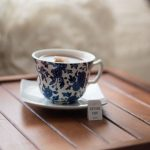 Cup of tea in a blue & white china tea set on a wooden table. The teabag label says Drink Me
