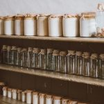 Three wooden shelves filled with jars. The middle shelf has empty jars.