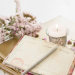 An open diary with a grey pen , a tea light candle in a grey ornate holder and some flowers.
