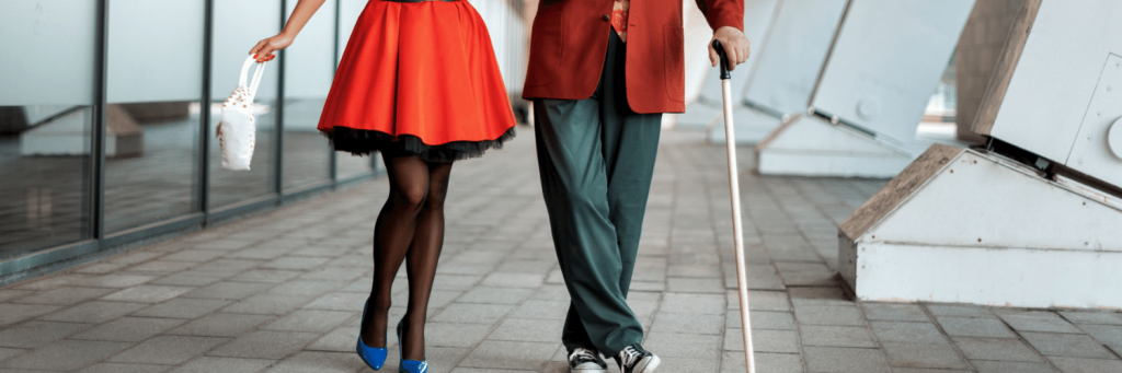 A person from the waist down wearing a red dancing skirt next to a person wearing pants and holding a walking stick.