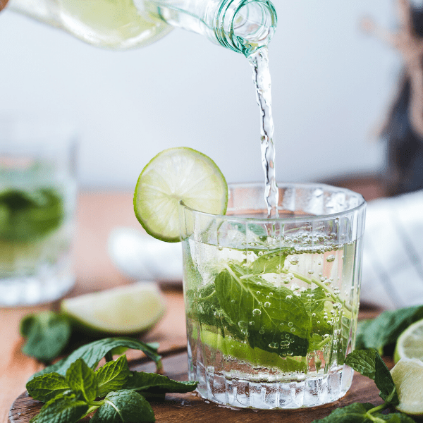 A bottle is pouring water into a glass that is filled with mint and has a lime garnish. The glass is on a wooden board with mint and wedges of lime.