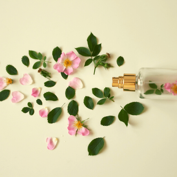A flatlay of leaves and pink flowers surrounding a clear spray bottle containing pink flowers.