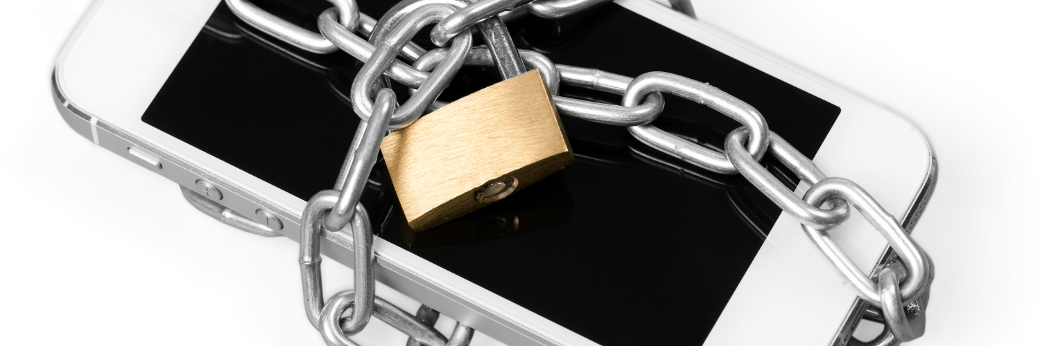 Close up of a smart phone wrapped in a chain and padlocked.