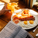 "A plate of eggs and bacon with someone holding a glass of juice and a paper that says ""this is what being in love reall means, because it's not all sex and kisses""."