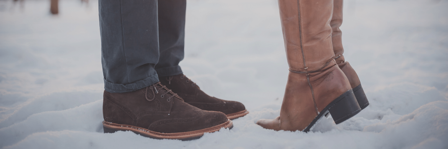 Two people from the knee down. They are both wearing boots and one is on tip toe. They are in the snow with trees in the background.
