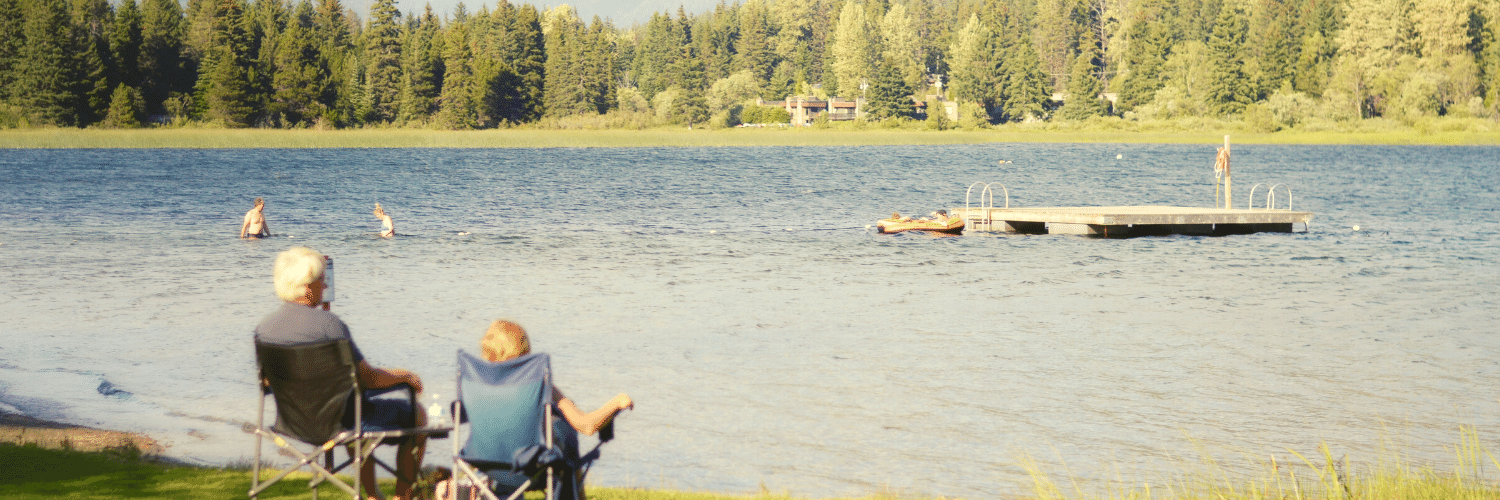 Two white haired people on camping chairs overlooking a river with a moutain and forest scene in the background.