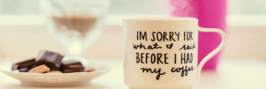 """A coffee cup that says """"I'm sorry for what I said before I had my coffee"""" there are biscuits on a plate and a pink vase of flowers."""