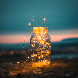 A mason jar filled with fairy lights, against a sunset background.