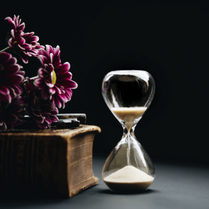 Image of an hourglass with sand falling through next to a book and some deep purple gerberas.
