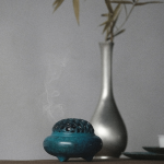 A small blue ceramic incense burner with smoke coming out, and a silver vase with bamboo in it.