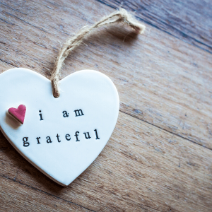 "A white heart on a wooden surface. Heart has the words ""I am grateful"""