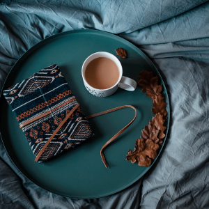 Turquoise tray on a bed with a cup of tea, a clothbound journal, and some autumn leaves.