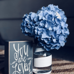"A hydrangea in a jar with a sign that says ""You are Loved"""