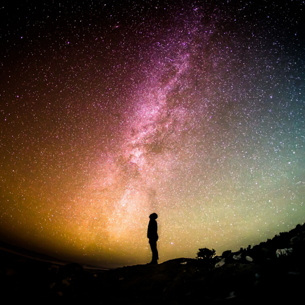 The small silhouette of a person looking at the night sky