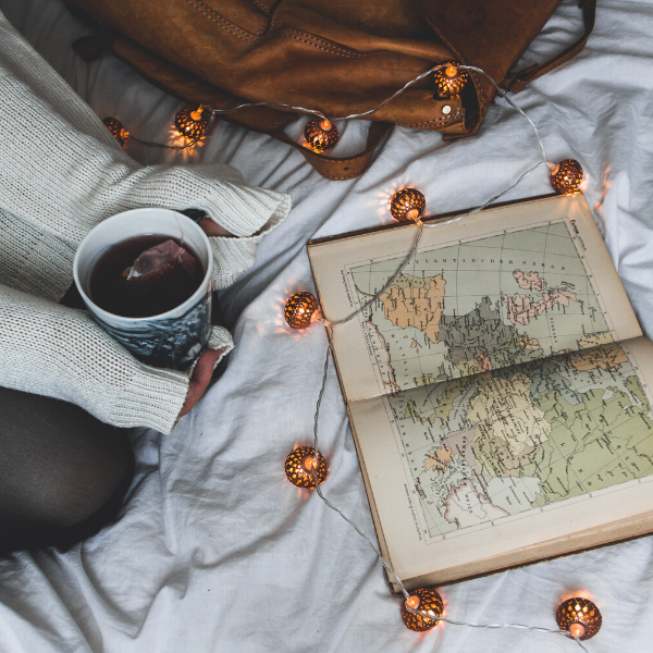 An open book with a map of the world on a bed. There is a person holding a cup of tea sitting on the bed, and a string of lights.