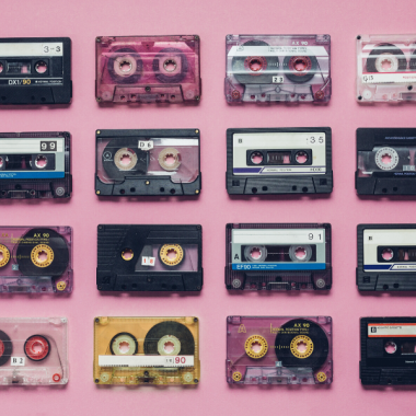 A series of cassette tapes against a pink background.