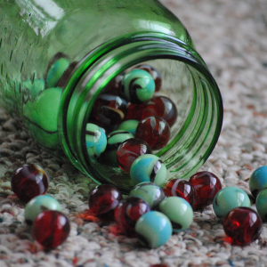 A green jar on its side on carpet with marbles spilling out.