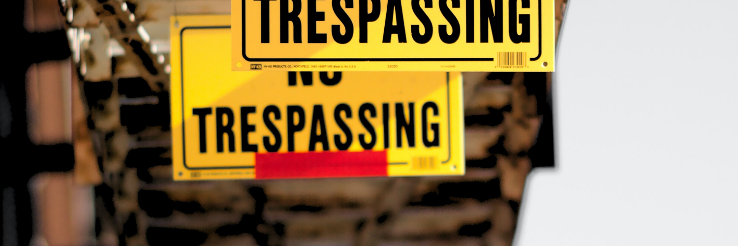 """Two yellow signs that say """"no trespassing"""" hanging beneath a metal staircase."""