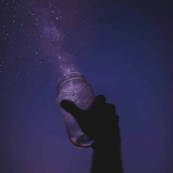 A hand silhouetted against the night sky holding a jar. It looks like the stars are coming out of the jar.