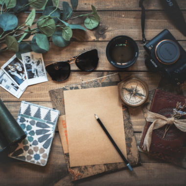 A flatlay with a journal and a pencil, surrounded by photos, sunglasses, a compass, binoculars and a plant.