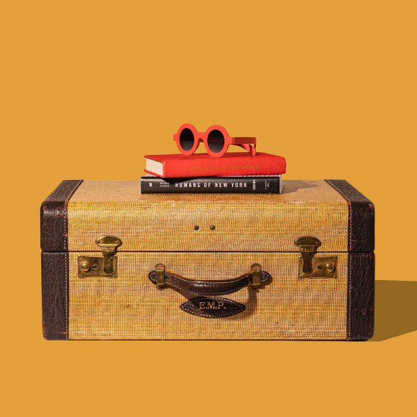 A piece of vintage luggage on a yellow background with books and sunglasses on top.