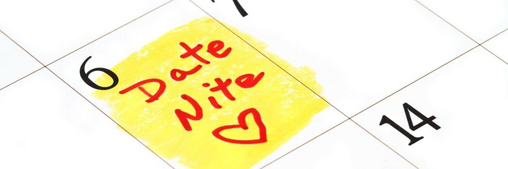 """A closeup of a calendar page with the 6th highlighted and """"Date Nite"""" with a heart written in red."""