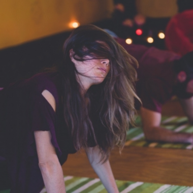 A woman on her hands and knees on a yoga mat with her hair partially covering her face.