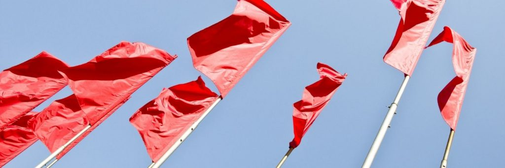 A line of red flags against a blue sky.