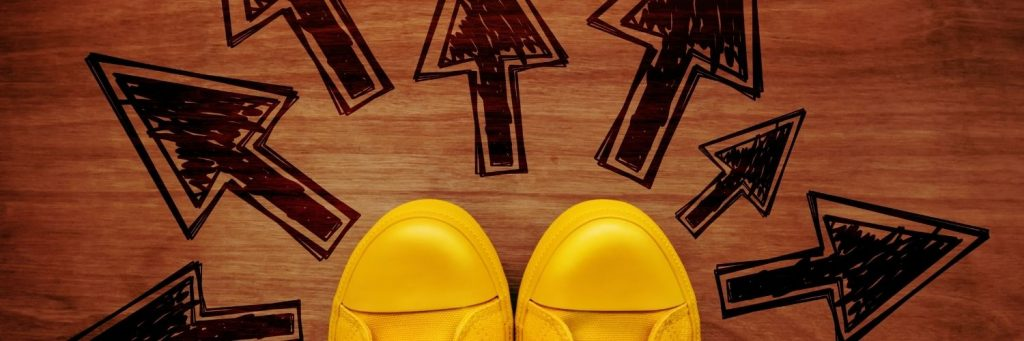 A pair of yellow sneakers with a series of arrows drawn on the ground in front pointing different directions.