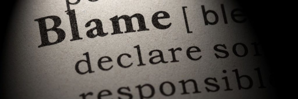 Closeup of a dictionary definition of the word 'blame'.